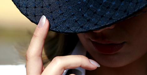 Dame mit Hut und 2 modellierte Fingenaegel im Luxus Nagelstudio. Stilvolle Nagelmodellage fuer Naturnaegel.