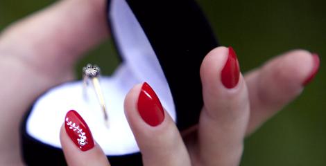 Schmucknaegel, Nailart oder Nageldesign aus dem Nagelstudio. Eine Hand mit rot lackierten Fingernaegeln und am kleinen Finger ist eine passende Verzierung mit weissem Nagellack zu sehen. Die Stuttgarter Luxus Kollektion.
