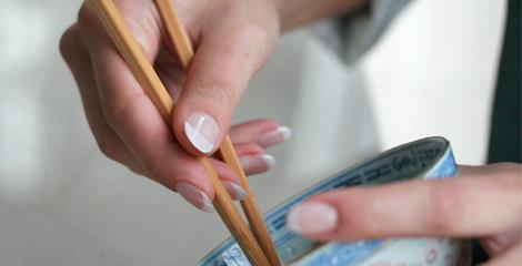 Nagelformen, Nagelkauer mit kuenstlichen Fingernaegeln aus dem Nagelstudio. Hand haelt eine Chinesische Schale mit Staebchen. Fingernaegel mit natur weissen Spitzen im French Look. Die Nagelform fuer schoene Haende.