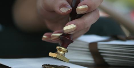 Eine Hand mit modellierten Fingernaegel aus Porcellan im Nagelstudio. Die Hand haelt einen Petschaft.Geschaedigte Naturnaegel werden regenerriert mit Pflegeprodukten aus den Nagelstudio Stuttgart mit der Serie Vernis Prive.