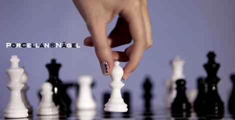 Nagelmodellage mit Porcellan, Daumen und Zeigefinger mit Schachfigur. Schoene natuerliche Fingernaegel. Fingernaegel aus dem Nagelstudio